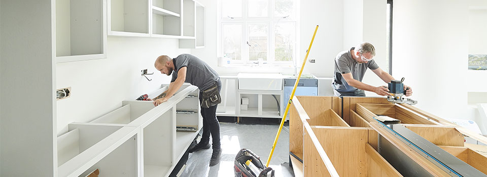 Two men working on kitchen cabinets